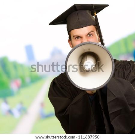 Graduate Man Holding Megaphone, Outdoor - stock photo