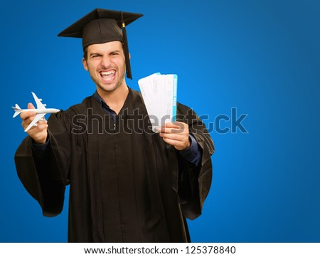 Graduate Man Holding Miniature Airplane And Boarding Pass On Blue Background