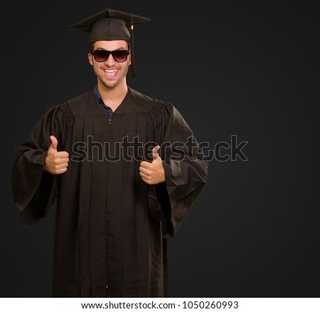 Graduate Man With Double Thumb Up Sign Isolated On Black Background