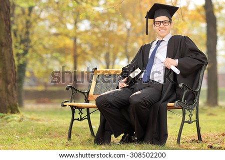 Graduate student holding diploma and a book seated on bench in park - stock photo