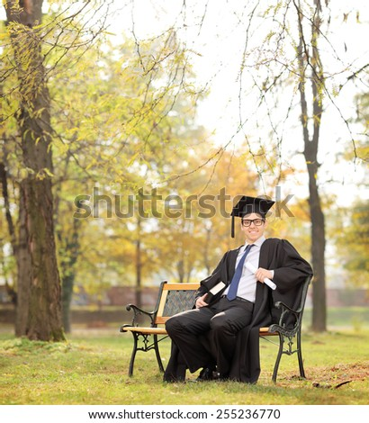 Graduate student holding diploma and a book seated on bench in park shot with tilt and shift lens