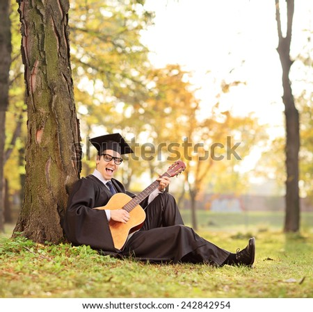 Graduate student playing acoustic guitar in park shot with a tilt and shift lens - stock photo
