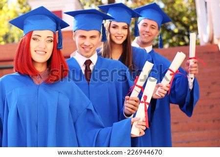 Graduate students with diplomas, outdoors - stock photo