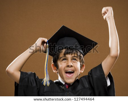 Graduated boy with mortarboard cheering - stock photo