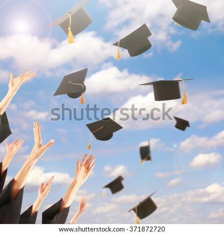 Graduates hands throwing graduation hats in the sky - stock photo