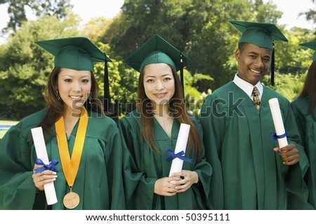 Graduates hoisting diplomas outside university, portrait