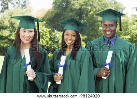 Graduates Holding Diplomas - stock photo