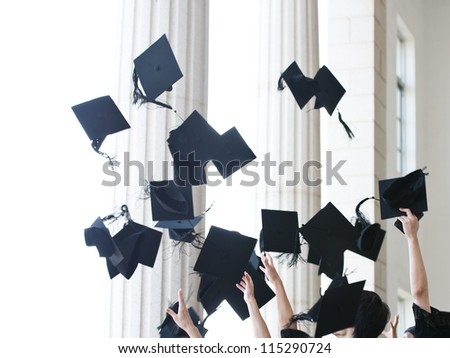 graduates throwing graduation hats in the air. - stock photo