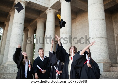 Graduates throwing their hats in the sky in front of their university - stock photo