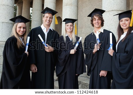 Graduates together in front of their university