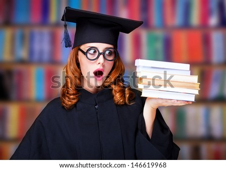 graduating student girl in an academic gown with books - stock photo
