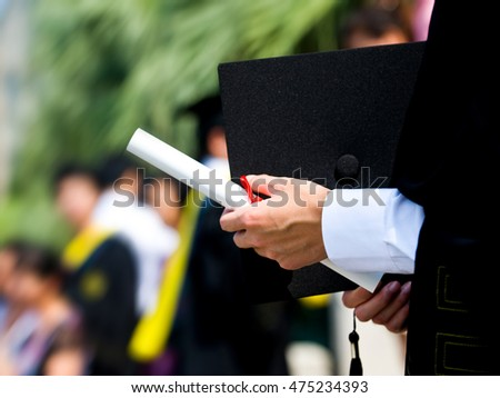 graduating student holding their diploma proudly.