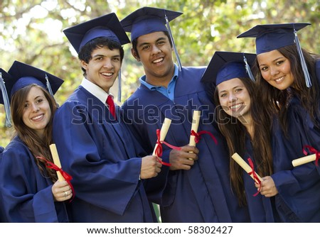 Graduating students smiling and laughing with diplomas; trees in background - stock photo