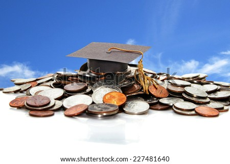 graduation cap on a pile of money  - stock photo