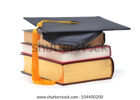 graduation cap on stacked books - stock photo