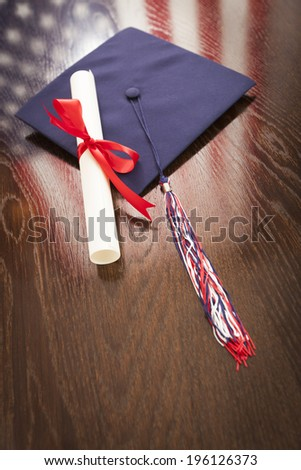 Graduation Cap with Tassel and Diploma Wresting on Wooden Table with American Flag Reflection.