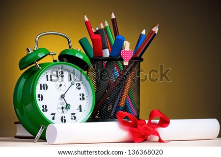 Graduation concept - school accessories on dark yellow background - stock photo