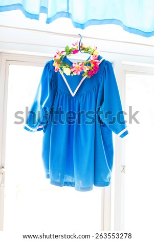 Graduation Day. A gown, tassel, and diploma and laid hanging on window ready for graduation day. - stock photo
