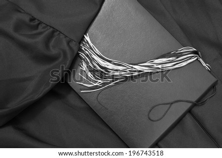 Graduation Day. A gown, tassel, and diploma and laid out ready for graduation day.  - stock photo