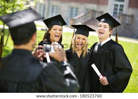 Graduation: Friends Smile As Guy Takes Photo - stock photo