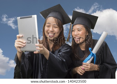 Graduation friends taking photo with tablet computer - stock photo
