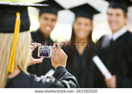Graduation: Girl Takes Photo of Friends After Ceremony - stock photo