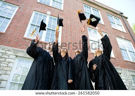Graduation: Graduates Toss Caps in Air In Celebration - stock photo