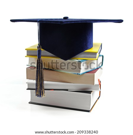 graduation hat and stack of books isolated on white - stock photo
