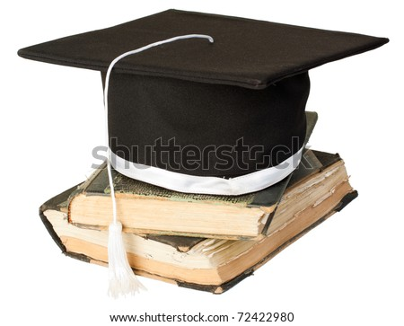 Graduation hat on a pile of old books. - stock photo