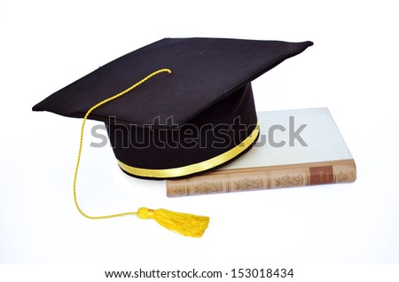 Graduation hat with old book - stock photo