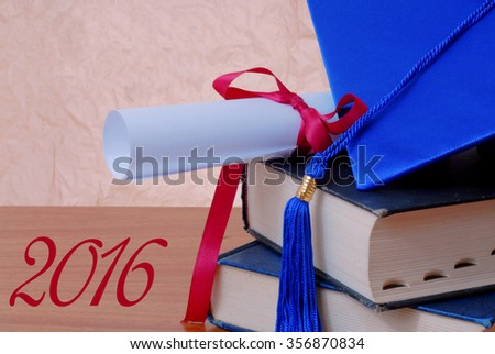 Graduation 2016 image includes blue cap and tassel and rolled up diploma tied with red ribbon on stacked books and text for 2016. Rough textured background and wooden table. Horizontal composition - stock photo
