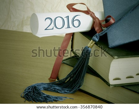 Graduation 2016 image includes blue cap and tassel and rolled up diploma tied with red ribbon on stacked books and text for 2016. Rough textured background and wooden table. Vintage filter applied. - stock photo