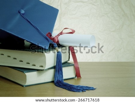 Graduation image of stacked books, diploma and graduation cap with tassel. Vignette and desaturation added for vintage look. Blue cap and tassel, ribbon on diploma is red. Rough textured background - stock photo