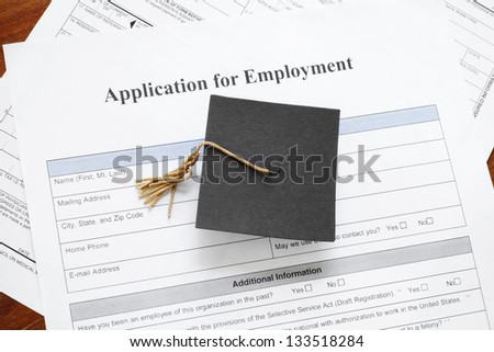 graduation mortar board cap on job application form - underemployent concept - stock photo
