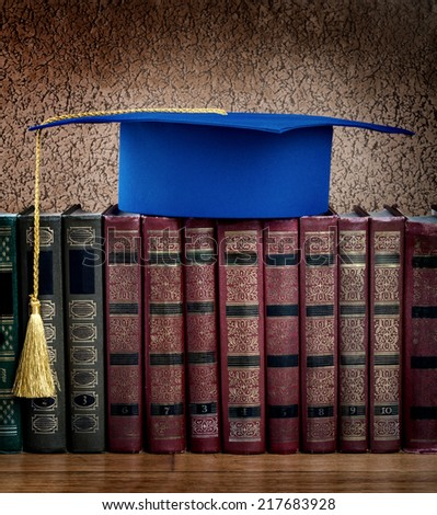 Graduation mortarboard on top of stack of books on abstract background of wall - stock photo