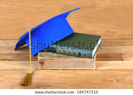 Graduation mortarboard on top of stack of books on the wooden table - stock photo