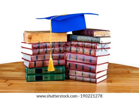 Graduation mortarboard on top of stack of books on white isolated background  - stock photo