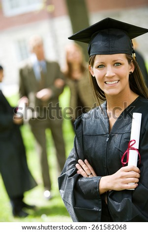 Graduation: Proud Female Graduate with Diploma With Family Behind - stock photo