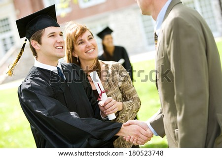 Graduation: Student Shakes Hands With Father - stock photo