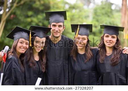 graduation students looking very happy outdoors - stock photo