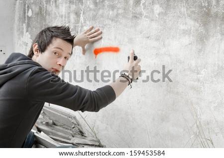 Graffiti artist about to start spraying a wall, looking at camera - stock photo