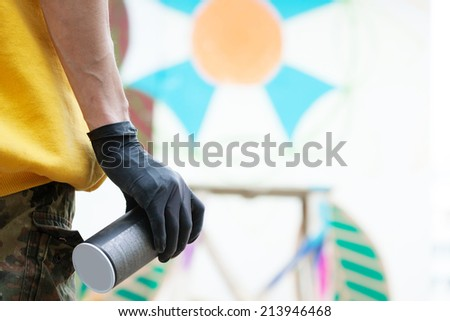 Graffiti artist's hand with spray can, close-up - stock photo