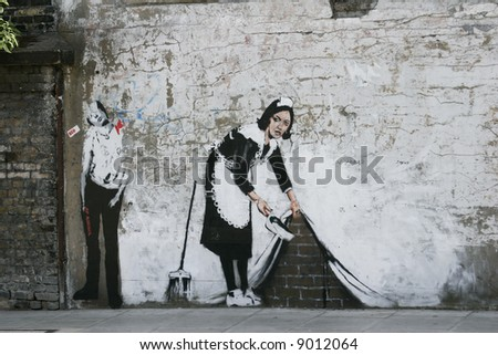 graffiti in an alley - Maid Sweeping by Banksy