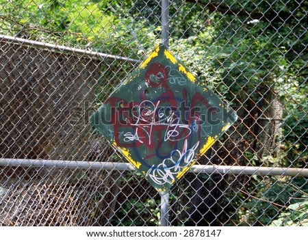 Graffiti on sign with chain link fence - stock photo