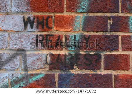 Graffiti on wall with the message who really cares, London England UK