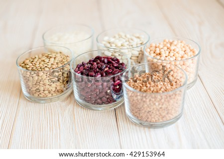 Grain and beans in glass bowls on white wooden background
