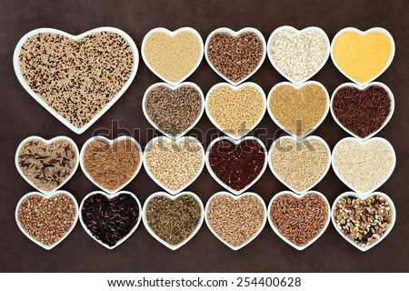 Grain and cereal food selection in heart shaped porcelain bowls over lokta paper background. Tricolour quinoa in large dish. - stock photo
