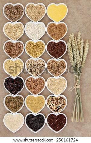 Grain and cereal food selection in heart shaped porcelain bowls over rough brown paper background with wheat ears. - stock photo