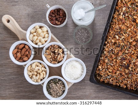 Grain free oat free paleo granola: mixed nuts, seeds, raisins, coconut flakes, chia and coconut oil, selective focus - stock photo
