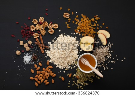 Grain free oat free paleo granola: mixed nuts, seeds, raisins, honey and coconut oil,  black background - stock photo